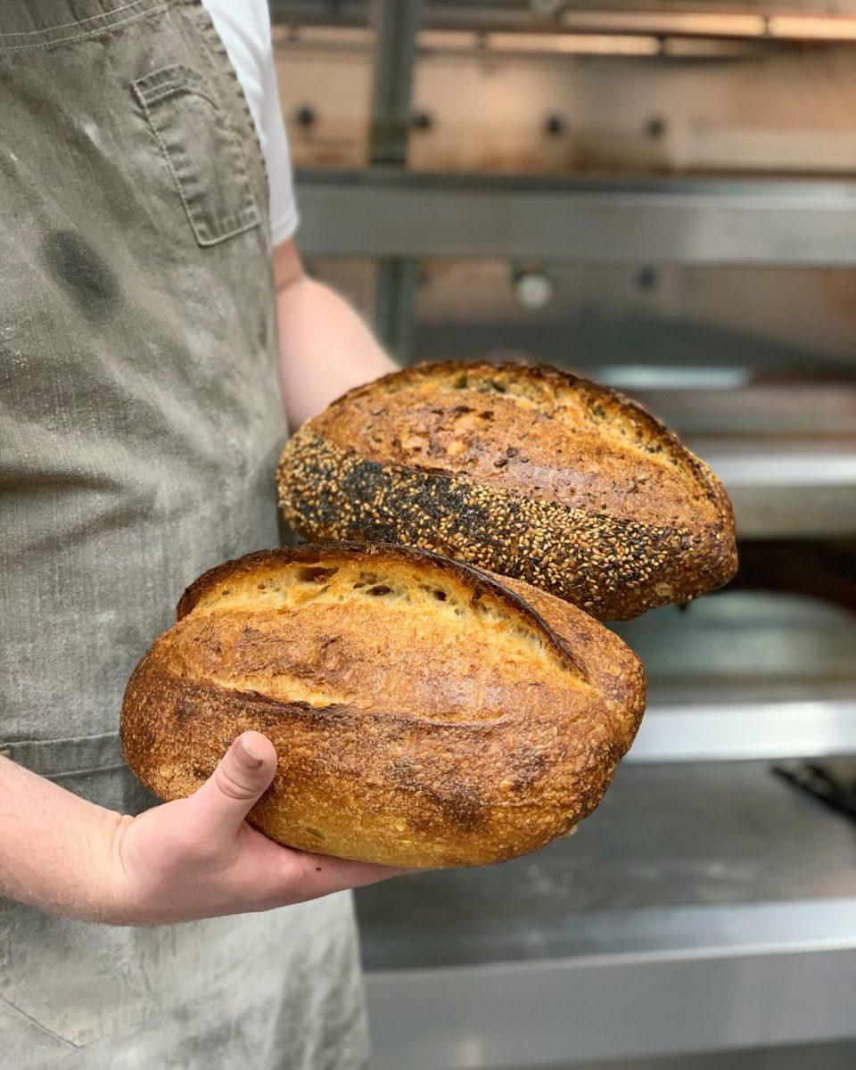 Baker holding two freshly baked loaves at Q Le Baker.